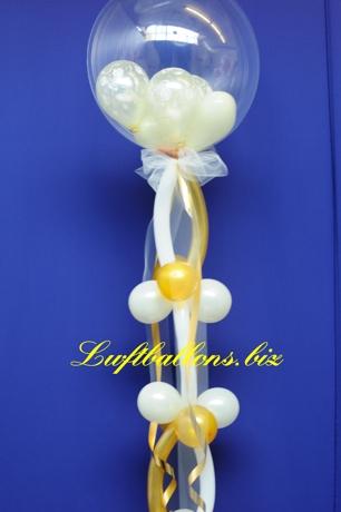 Bild. Transparenter Bubble-Luftballon, dekoriert mit Luftballons aus Latex, Zierschleife und Zierbändern.
