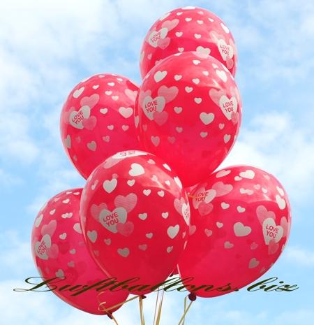 Bild. Rund-Luftballons bedruckt mit weißen Herzen, I Love You, mit Helium gebündelt in einer Ballontraube